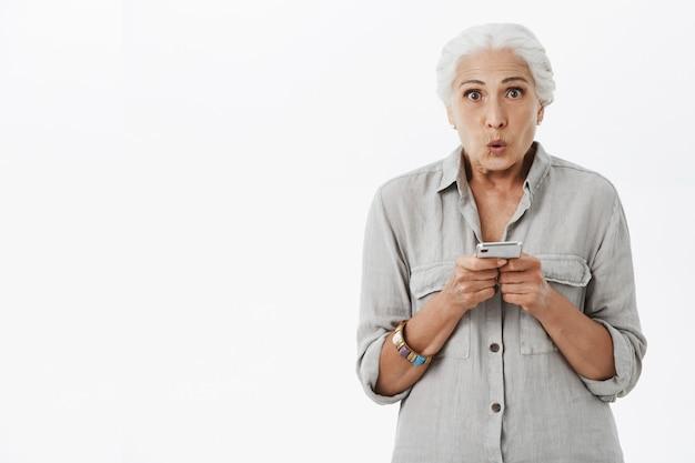 Onder de indruk senior vrouw zegt wow, gebruikt mobiele telefoon en kijkt verbaasd
