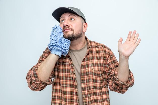 Onder de indruk slavische schonere man met microfiber reinigingshandschoen en kijkend naar de zijkant