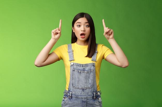 Onder de indruk sprakeloos geschokt aziatisch meisje, wijzende vingers omhoog, laten vallen van de kaak hijgend verbaasd, staren camera verbaasd, vertellen over ongelooflijke prijzen nieuwe producten, staan groene achtergrond