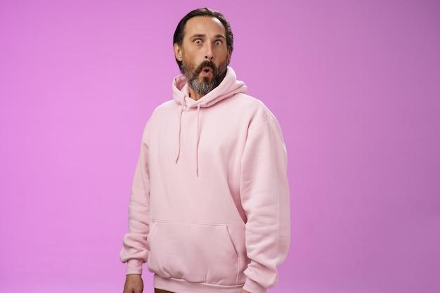 Onder de indruk sprakeloos geschokt volwassen bebaarde man grijs haar in koele roze hoodie vouwende lippen wow knallende ogen camera verrast verbaasd geïntrigeerd, staand nieuwsgierig verbaasd paarse achtergrond.