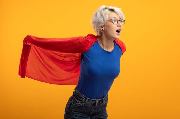 Onder de indruk supervrouw in optische bril houdt rode cape en kijkt naar kant geïsoleerd op oranje muur