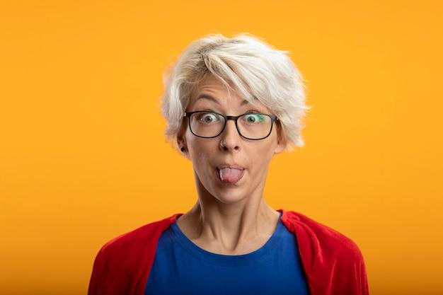 Onder de indruk supervrouw met rode cape in optische glazen steekt tong uit die op oranje muur wordt geïsoleerd