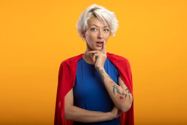 Onder de indruk supervrouw met rode cape legt hand op kin geïsoleerd op oranje muur