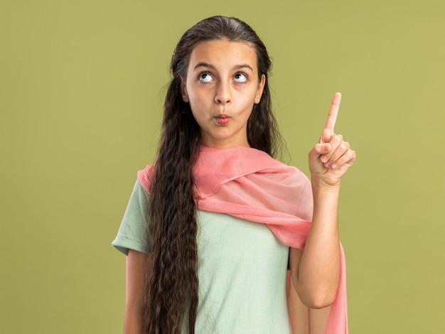 Onder de indruk tienermeisje met een sjaal die kijkt en omhoog wijst met getuite lippen geïsoleerd op een olijfgroene muur
