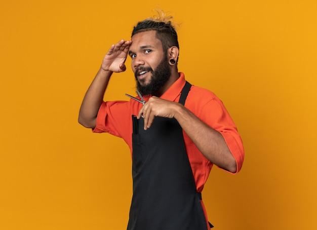 Onder de indruk van de jonge afro-amerikaanse mannelijke kapper die een uniform draagt staand in profielaanzicht met een schaar die de hand op het voorhoofd houdt en naar voren kijkt in de verte