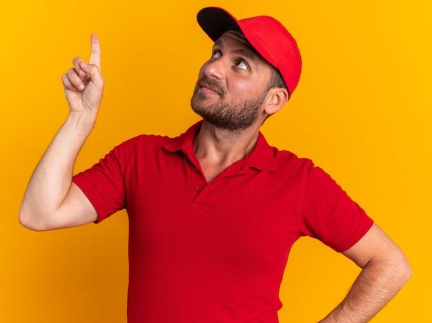 Onder de indruk van de jonge blanke bezorger in rood uniform en pet die de hand op de taille houdt en omhoog wijst, geïsoleerd op een oranje muur