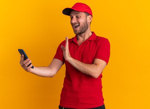 Onder de indruk van de jonge blanke bezorger in rood uniform en pet die mobiele telefoon vasthoudt en kijkt terwijl hij hallo gebaar doet geïsoleerd op een oranje muur