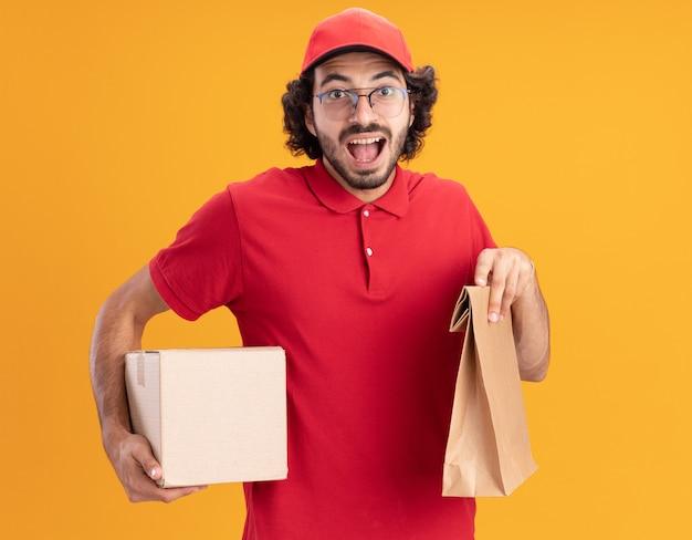 Onder de indruk van de jonge blanke bezorger in rood uniform en pet met een bril met een kartonnen doos en een papieren pakket geïsoleerd op een oranje muur