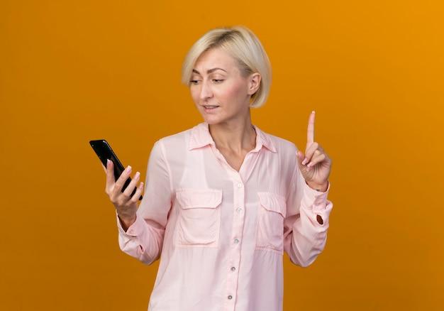 Onder de indruk van de jonge blonde slavische vrouw die omhoog houdt en naar telefoonpunten kijkt