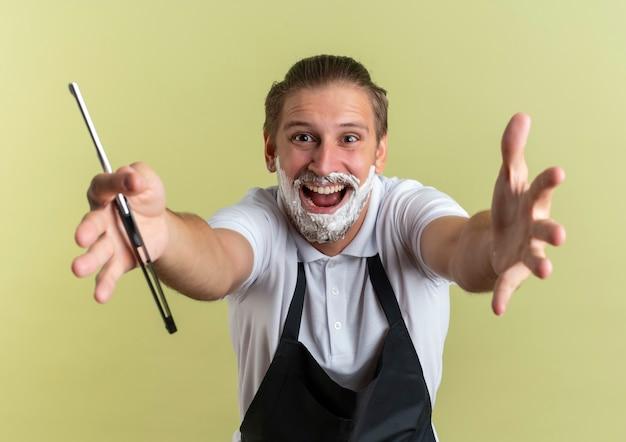 Onder de indruk van de jonge knappe kapper die uniform draagt die zich uitstrekt met de hand en een scheermes naar de camera met scheerschuim aangebracht op zijn gezicht geïsoleerd op olijfgroen