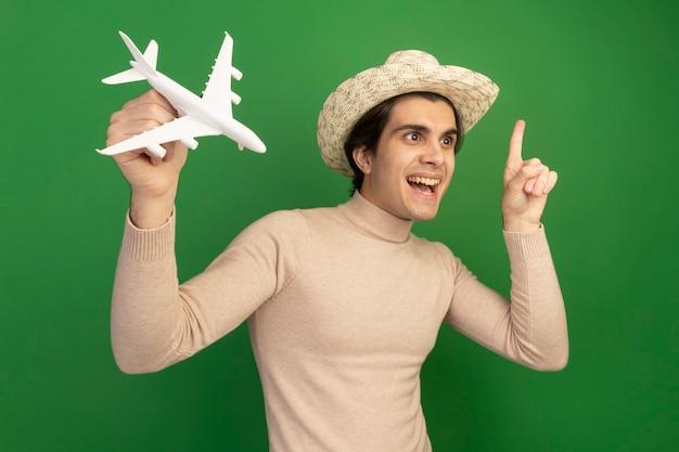 Onder de indruk van de jonge knappe kerel die aan de zijkant een hoed draagt en speelgoedvliegtuig richt op omhoog geïsoleerd op groene muur