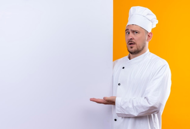 Onder de indruk van de jonge knappe kok in uniform van de chef-kok die achter een witte muur staat en met de hand wijst naar het geïsoleerd op een oranje muur met kopieerruimte