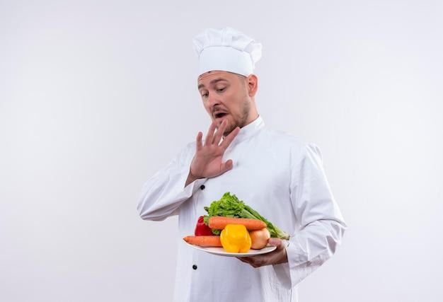 Onder de indruk van de jonge knappe kok in uniform van de chef-kok die een bord met groenten vasthoudt en de hand boven hen houdt op een geïsoleerde witte muur met kopieerruimte