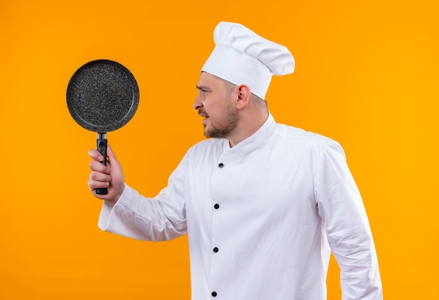 Onder de indruk van de jonge knappe kok in uniform van de chef-kok die een koekenpan vasthoudt die naar de zijkant kijkt die op een oranje muur is geïsoleerd