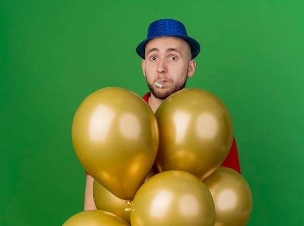 Onder de indruk van de jonge knappe slavische feestjongen die feestmuts draagt die achter ballonnen staan kijken naar camera waait partijblazer geïsoleerd op groene achtergrond met kopie ruimte