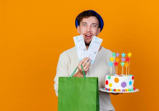 Onder de indruk van de jonge knappe slavische feestjongen die feestmuts draagt die vliegtuigtickets papieren zak en verjaardagstaart met sterren kijken naar camera geïsoleerd op een oranje achtergrond met kopie ruimte