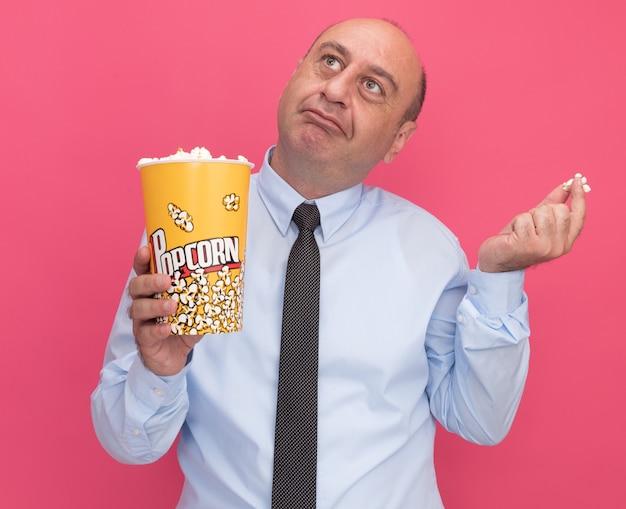 Onder de indruk van de man van middelbare leeftijd die een wit t-shirt met stropdas draagt en een emmer popcorn met een stuk popcorn houdt dat op roze muur wordt geïsoleerd