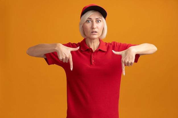 Onder de indruk van een blonde bezorger van middelbare leeftijd in een rood uniform en een pet die naar de voorkant kijkt en naar beneden wijst, geïsoleerd op een oranje muur