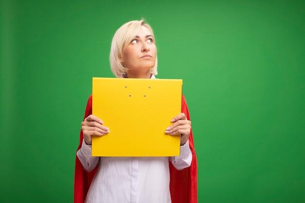 Onder de indruk van een blonde superheldenvrouw van middelbare leeftijd in een rode cape die een map vasthoudt en naar de zijkant kijkt