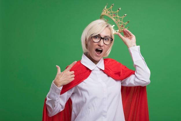 Onder de indruk van een blonde superheldenvrouw van middelbare leeftijd in een rode cape met een bril die een kroon boven het hoofd houdt en naar zichzelf wijst