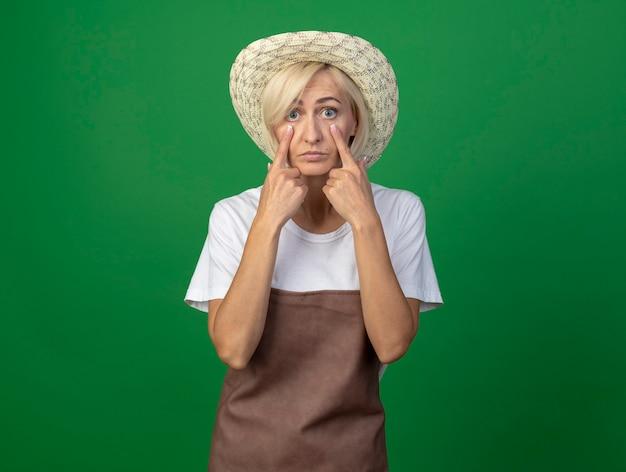 Onder de indruk van een blonde tuinmanvrouw van middelbare leeftijd in uniform met een hoed die oogleden naar beneden trekt, geïsoleerd op een groene muur met kopieerruimte