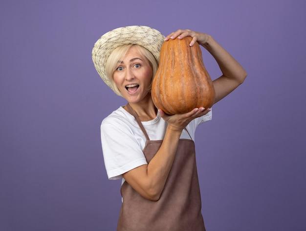 Onder de indruk van een blonde tuinmanvrouw van middelbare leeftijd in uniform met een hoed met een pompoen in de buurt van het hoofd