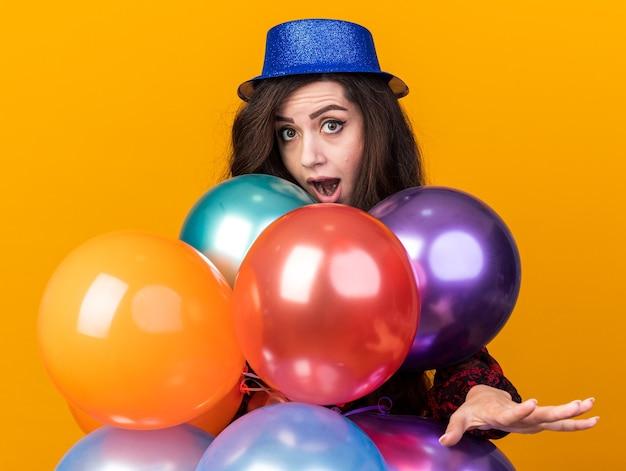 Onder de indruk van een jong feestmeisje met een feesthoed die achter ballonnen staat en naar de camera kijkt die de hand uitstrekt die op een oranje muur is geïsoleerd