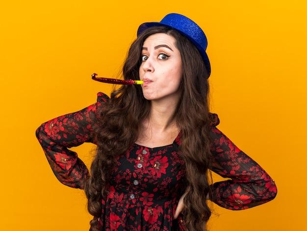 Onder de indruk van een jong feestmeisje met een feesthoed die de handen op de taille houdt en een feesthoorn blaast, geïsoleerd op een oranje muur
