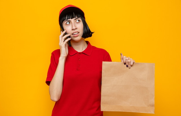 Onder de indruk van een jong kaukasisch bezorgmeisje dat papieren voedselverpakkingen vasthoudt en telefoneert