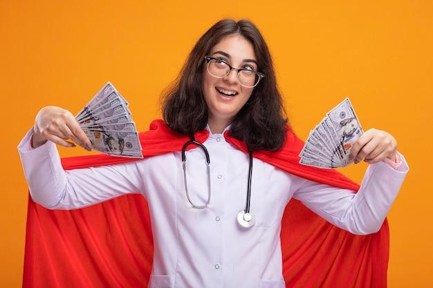 Onder de indruk van een jong kaukasisch superheldenmeisje met een doktersuniform en een stethoscoop met een bril die geld vasthoudt en omhoog kijkt geïsoleerd op de muur