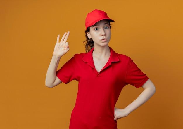 Onder de indruk van een jong, mooi bezorgmeisje in een rood uniform en een pet die de hand op de taille legt en een goed teken doet