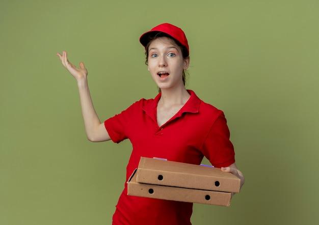 Onder de indruk van een jong, mooi bezorgmeisje in een rood uniform en een pet die pizzapakketten vasthoudt en lege hand toont showing