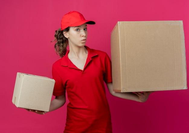Onder de indruk van een jong, mooi bezorgmeisje in een rood uniform en een pet met kartonnen dozen die op karmozijnrode ruimte kijken
