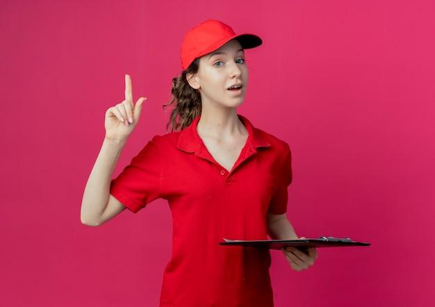 Onder de indruk van een jong, mooi bezorgmeisje in een rood uniform en een pet met klembord en een vinger op de karmozijnrode ruimte