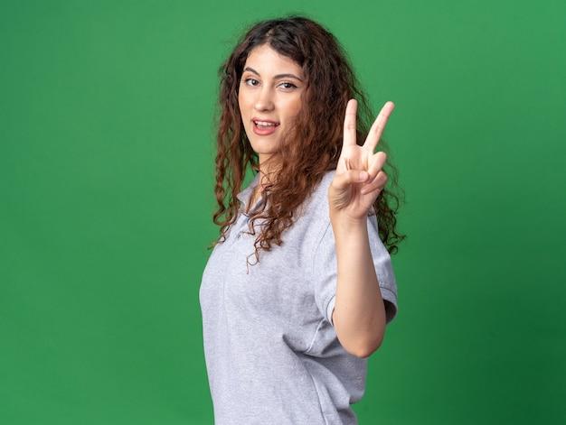 Onder de indruk van een jong, mooi kaukasisch meisje dat in profielweergave staat en vredesteken doet geïsoleerd op een groene muur met kopieerruimte