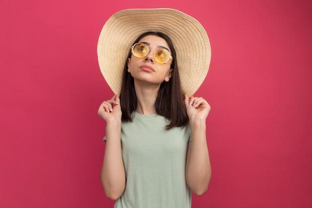 Onder de indruk van een jong, mooi kaukasisch meisje met een strandhoed en een zonnebril die een hoed grijpt en omhoog kijkt
