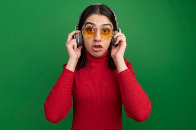 Onder de indruk van een jong, mooi kaukasisch meisje met een zonnebril en een koptelefoon die een koptelefoon grijpt en er recht uitziet geïsoleerd op een groene muur met kopieerruimte