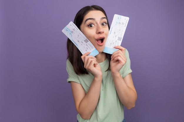 Onder de indruk van een jong, mooi kaukasisch meisje met vliegtuigkaartjes die het gezicht ermee raken