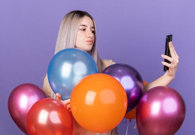Onder de indruk van een jong mooi meisje dat de telefoon vasthoudt en bekijkt die achter ballonnen staat geïsoleerd op een blauwe muur