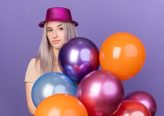 Onder de indruk van een jong mooi meisje met een feesthoed die achter ballonnen staat geïsoleerd op een blauwe muur