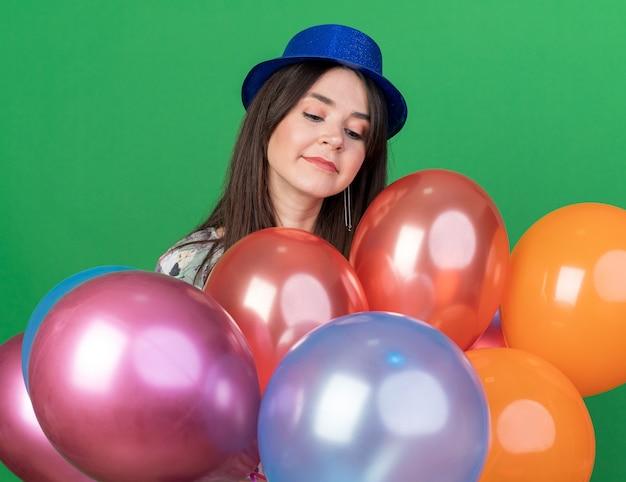 Onder de indruk van een jong mooi meisje met een feesthoed die achter ballonnen staat geïsoleerd op een groene muur
