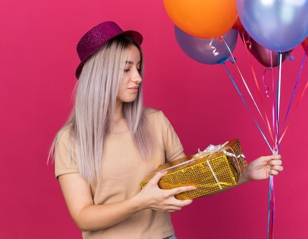 Onder de indruk van een jong mooi meisje met een feesthoed die ballonnen vasthoudt en naar een geschenkdoos in haar hand kijkt, geïsoleerd op een roze muur