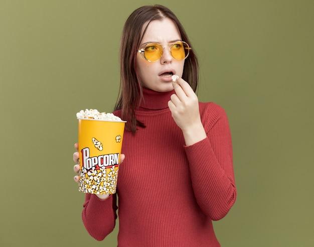 Onder de indruk van een jong mooi meisje met een zonnebril die een emmer popcorn en een stuk popcorn in de buurt van de mond vasthoudt en naar de zijkant kijkt