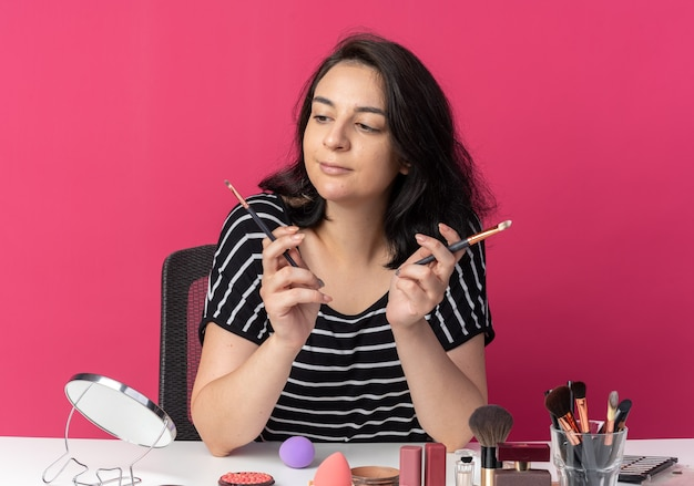Onder de indruk van een jong mooi meisje zit aan tafel met make-uptools die een poederborstel vasthouden en bekijken die op een roze muur is geïsoleerd