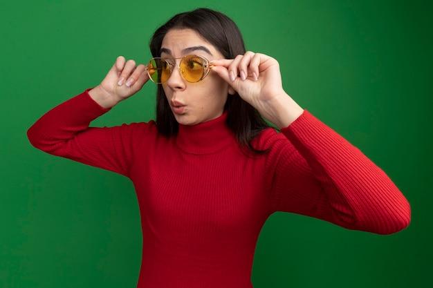 Onder de indruk van een jong, vrij kaukasisch meisje dat een zonnebril draagt en grijpt en naar de zijkant kijkt met getuite lippen