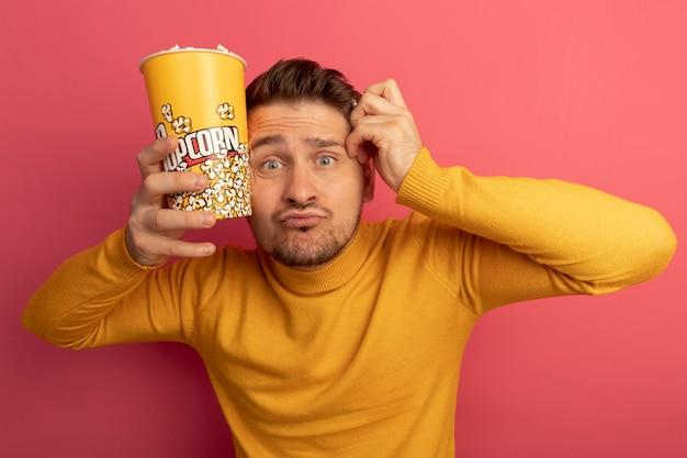 Onder de indruk van een jonge blonde knappe man met een emmer popcorn en een stuk popcorn die het hoofd aanraakt met een emmer popcorn en hand