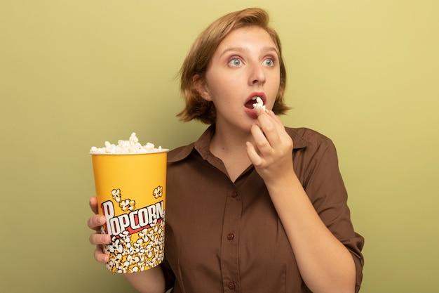 Onder de indruk van een jonge blonde vrouw met een emmer popcorn en een stuk popcorn in de buurt van de mond die naar de zijkant kijkt die op een olijfgroene muur is geïsoleerd