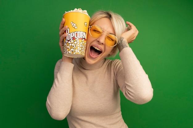 Onder de indruk van een jonge blonde vrouw met een emmer popcorn en stukjes popcorn die het gezicht aanraakt met een emmer popcorn en hand met gesloten ogen