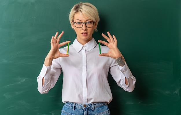 Onder de indruk van een jonge blonde vrouwelijke leraar met een bril in de klas die voor een bord staat met telstokken die naar de camera kijken