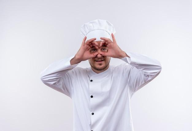 Onder de indruk van een jonge knappe kok in uniform van de chef-kok die een gebaar maakt met de handen als verrekijker op een geïsoleerde witte muur